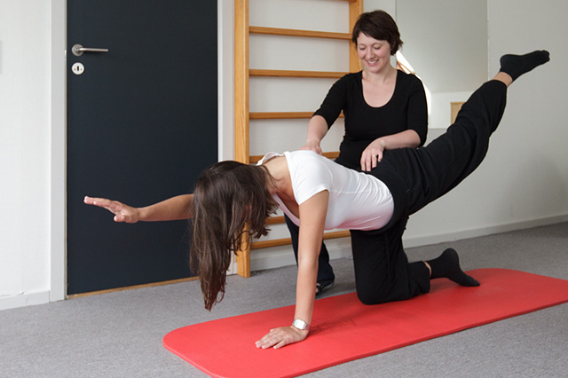 Billede af en pige, der under vejledning laver stabilitetstræning